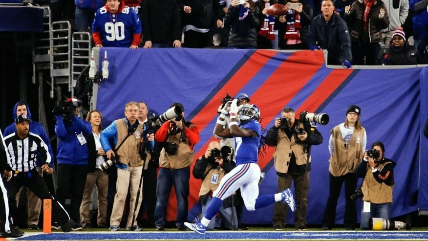 Fans watch as New York Giants wide receiver Dwayne Harris (17) waits for the ball on a touchdown reception during the first half of an NFL football game against the New England Patriots on Sunday, Nov. 15, 2015, in East Rutherford, N.J. (AP Photo/Julio Cortez)