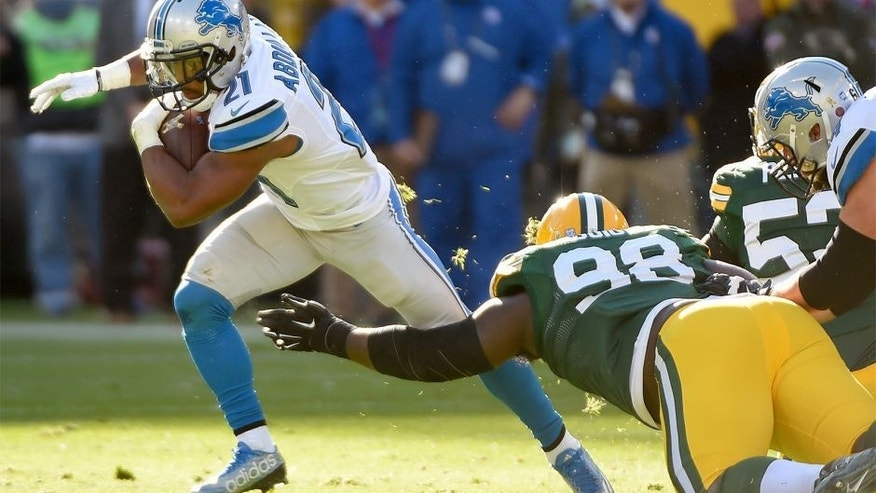 Nov 15, 2015; Green Bay, WI, USA; Detroit Lions running back Ameer Abdullah (21) tries to avoid a tackle by Green Bay Packers defensive tackle Letroy Guion (98) in the second quarter at Lambeau Field. Mandatory Credit: Benny Sieu-USA TODAY Sports