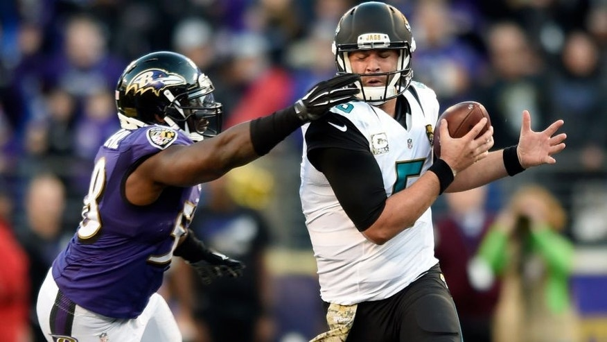 Baltimore Ravens outside linebacker Elvis Dumervil, left, grabs Jacksonville Jaguars quarterback Blake Bortles' face mask in the second half an NFL football game, Sunday, Nov. 15, 2015, in Baltimore. Jacksonville kicked the winning field goal after Baltimore received a face mask penalty on the play. Jacksonville won 22-20. (AP Photo/Gail Burton)
