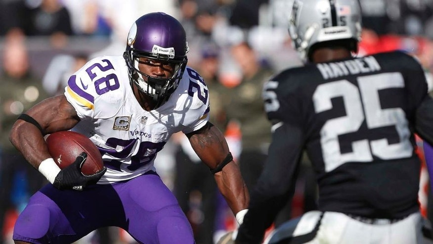 Minnesota Vikings running back Adrian Peterson runs against Oakland Raiders cornerback D.J. Hayden during the first half in Oakland, Calif., on Sunday, Nov. 15, 2015.