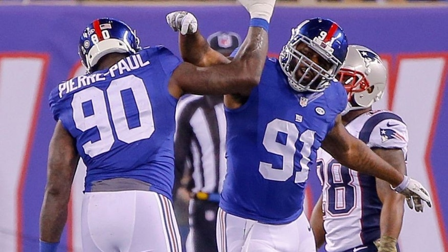 Nov 15, 2015; East Rutherford, NJ, USA; New York Giants defensive end Jason Pierre-Paul (90) celebrates with defensive end Robert Ayers (91) during the fourth quarter against the New England Patriots at MetLife Stadium. Jason Pierre-Paul had to put protection on after hurting his hand by deflecting a pass during the first half. New England Patriots defeat the New York Giants 27-26. Mandatory Credit: Jim O'Connor-USA TODAY Sports