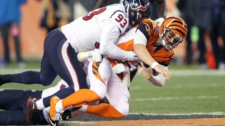 CINCINNATI, OH - NOVEMBER 16: Andy Dalton #14 of the Cincinnati Bengals is tackled by Benardrick McKinney #55 of the Houston Texans and Jared Crick #93 of the Houston Texans during the second quarter at Paul Brown Stadium on November 16, 2015 in Cincinnati, Ohio. (Photo by John Grieshop/Getty Images)