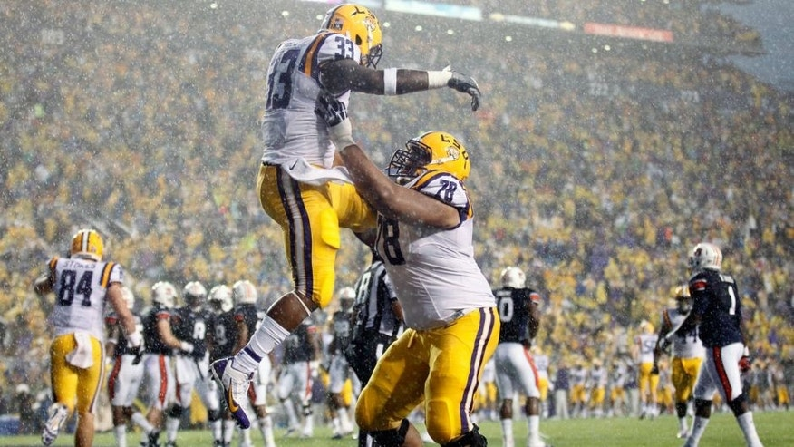 Sep 21, 2013; Baton Rouge, LA, USA; LSU Tigers running back Jeremy Hill (33) celebrates with offensive tackle Vadal Alexander (78) after a touchdown against the Auburn Tigers in the first quarter at Tiger Stadium. Mandatory Credit: Crystal LoGiudice-USA TODAY Sports