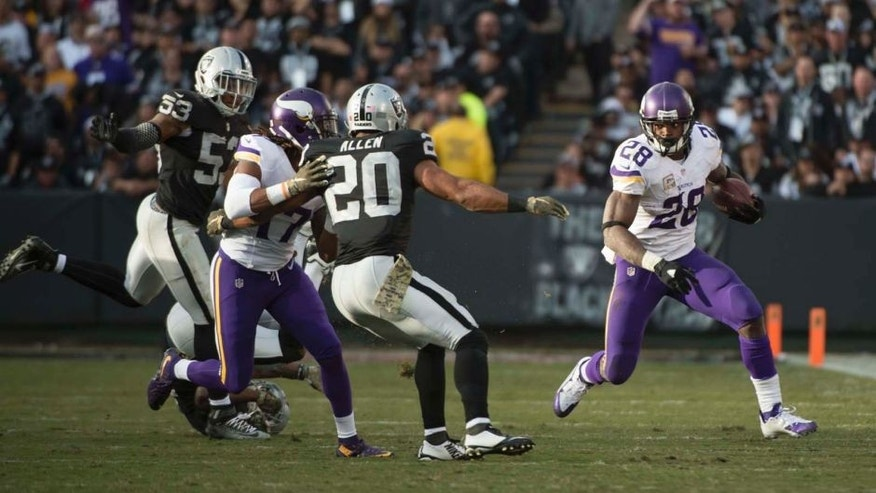 Minnesota Vikings running back Adrian Peterson runs with the football against Oakland Raiders strong safety Nate Allen during the fourth quarter at O.co Coliseum in Oakland, Calif., on Sunday, Nov. 15, 2015.