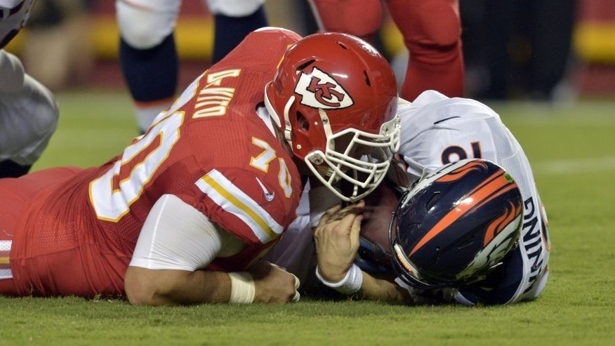 Sep 17, 2015; Kansas City, MO, USA; Denver Broncos quarterback Peyton Manning (18) is sacked by Kansas City Chiefs defensive end Mike DeVito (70) during the first half at Arrowhead Stadium. Mandatory Credit: Denny Medley-USA TODAY Sports