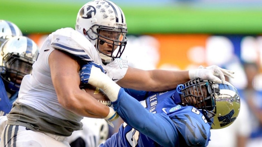 Dec 22, 2014; Miami, FL, USA; Brigham Young Cougars running back Algernon Brown (24) stiff arms Memphis Tigers defensive lineman Terry Redden (56) during the third quarter in the Miami Beach Bowl at Marlins Park. Memphis won 55-48 in a double overtime. Mandatory Credit: Steve Mitchell-USA TODAY Sports