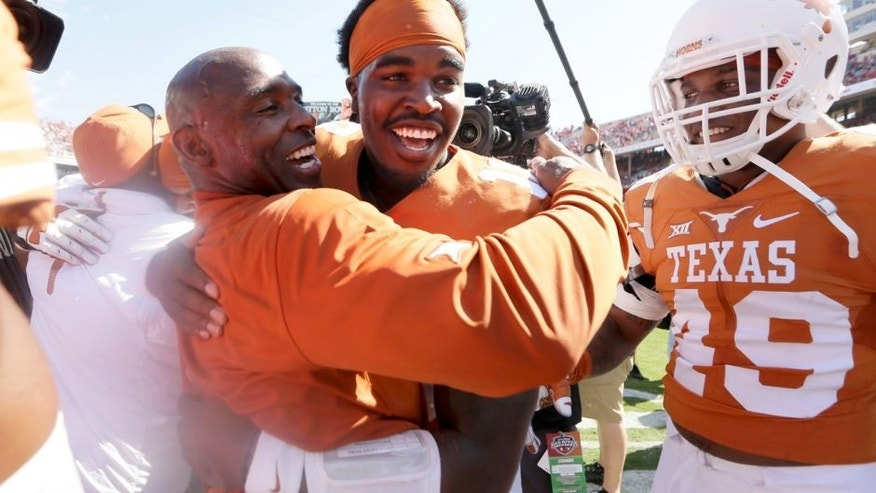 Texas head coach Charlie Strong,center left, celebrates with Tyrone Swoopes after their 24-17 win over Oklahoma in an NCAA college football game, Saturday, Oct. 10, 2015, in Dallas. (AP Photo/LM Otero)