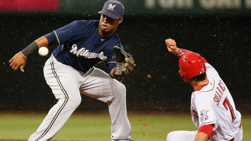 <p>Cincinnati Reds' Eugenio Suarez (7) beats the throw to second base against Milwaukee Brewers shortstop Jean Segura on a passed ball during the fourth inning in the second game of a baseball doubleheader, Saturday, Sept. 5, 2015, in Cincinnati. (AP Photo/John Minchillo)</p>