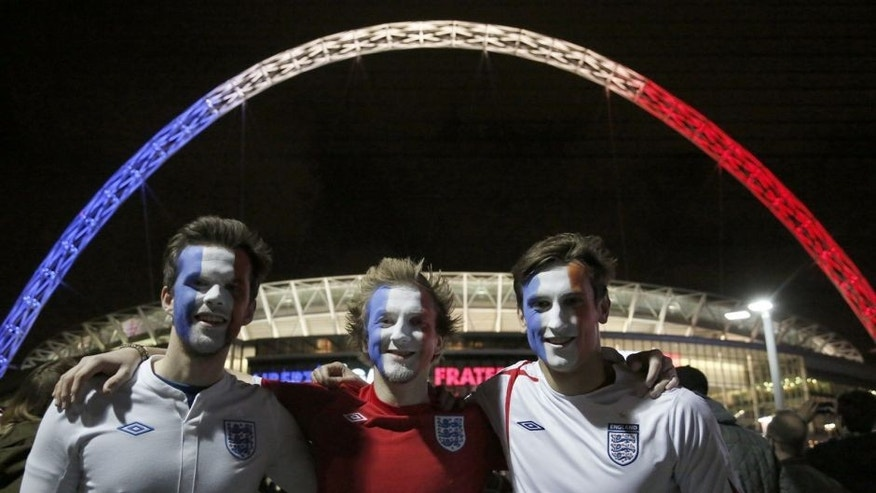 LONDON, ENGLAND - NOVEMBER 17: Football fans with their faces painted in the colors of Frenc flag are seen outside of Wembley Stadium, before the start of the friendly football match between England and France at Wembley Stadium in west London on November 17, 2015. (Photo by Yunus Kaymaz/Anadolu Agency/Getty Images)