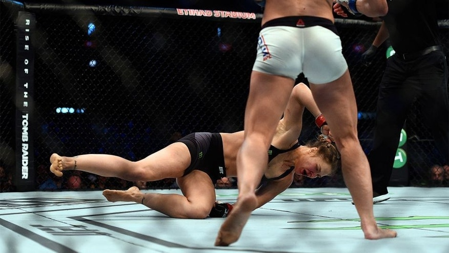 MELBOURNE, AUSTRALIA - NOVEMBER 15: (L-R) Ronda Rousey falls to the mat as she is knocked out by Holly Holm in their UFC women's bantamweight championship bout during the UFC 193 event at Etihad Stadium on November 15, 2015 in Melbourne, Australia. (Photo by Jeff Bottari/Zuffa LLC/Zuffa LLC via Getty Images)