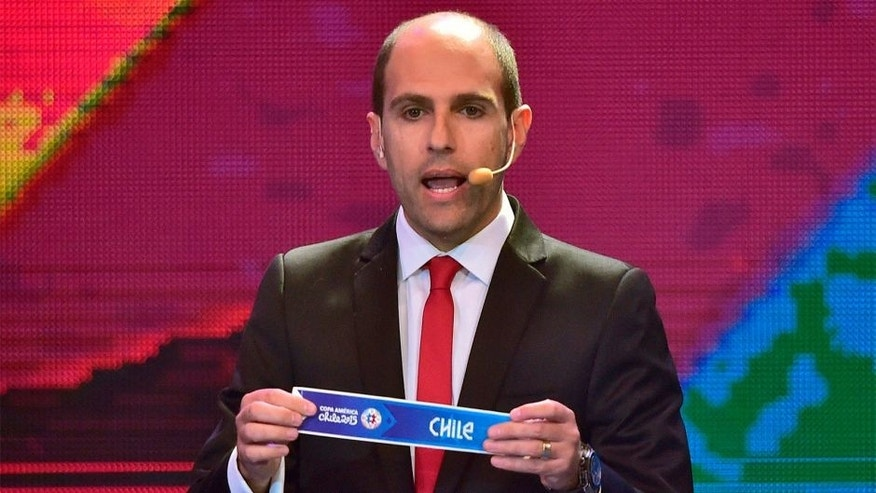 The president of Chile's Professional Football National Association (ANFP) Sergio Jadue, shows the name of Chile during the Copa America 2015 draw, at the Quinta Vergara in Vina del Mar, Chile, on November 24, 2014. The Copa America Chile 2015 will take place in eight Chilean cities, from June 11 to July 4, 2015. AFP PHOTO / MARTIN BERNETTI (Photo credit should read MARTIN BERNETTI/AFP/Getty Images)