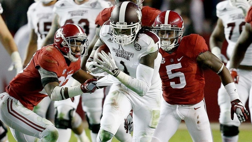 Nov 15, 2014; Tuscaloosa, AL, USA; Mississippi State Bulldogs wide receiver De'Runnya Wilson (1) is grabbed from behind by Alabama Crimson Tide defensive back Nick Perry (27) at Bryant-Denny Stadium. Mandatory Credit: Marvin Gentry-USA TODAY Sports