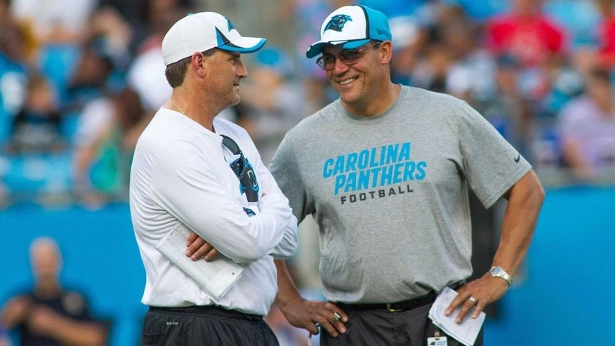Jul 25, 2014; Charlotte, NC, USA; Carolina Panthers offensive coordinator Mike Shula talks with head coach Ron Rivera during training camp at Bank of America Stadium. Mandatory Credit: Jeremy Brevard-USA TODAY Sports