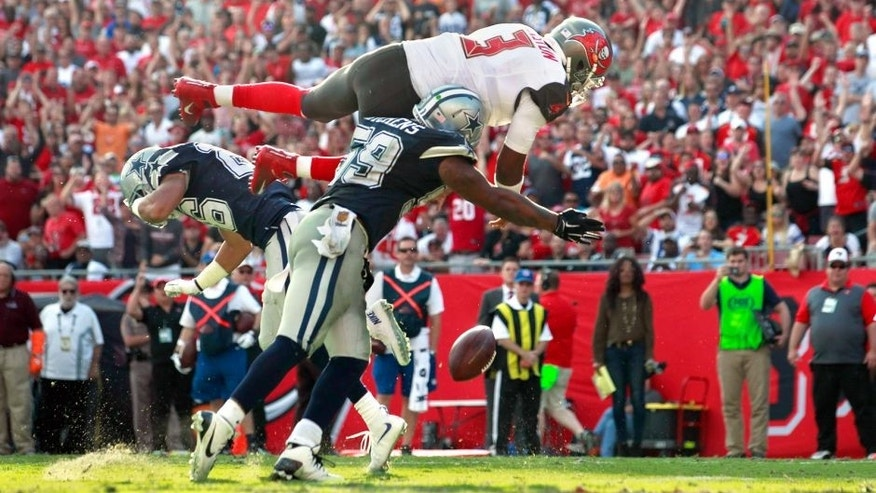 Nov 15, 2015; Tampa, FL, USA; Tampa Bay Buccaneers quarterback Jameis Winston (3) jumps over Dallas Cowboys middle linebacker Anthony Hitchens (59) and fumbles the ball during the second half at Raymond James Stadium. Mandatory Credit: Kim Klement-USA TODAY Sports