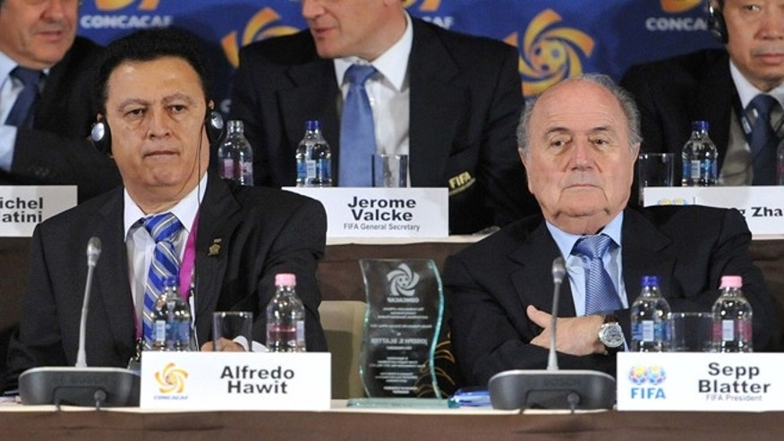 FILE - In this picture taken May 23, 2012 in Budapest, Hungary, Alfredo Hawit of Honduras, left, interim Head of CONCACAF and FIFA President Joseph Blatter sit next to each other. Swiss police carried out raids early Dec.3, 2015 in Zurich, Switzerland, against FIFA officials in connection with corruption investigations, the football's international governing body said. FIFA said it 'will continue to co-operate fully' after police made arrests at a Swiss hotel used by its officials for a second time this year. A two-day meeting of FIFA's executive committee is taking place in the in Zurich. The raids were carried out by Swiss authorities in the context of a US-led investigation, reports said.  (Szilard Koszticsak/MTI via AP/File)