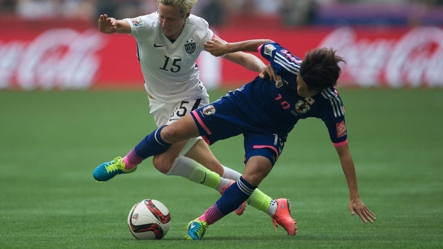 FILE - In this July 5, 2015, file photo, United States' Megan Rapinoe, left, and Japan's Homare Sawa fight for the ball during first half FIFA Women's World Cup soccer championship in Vancouver, British Columbia. American World Cup champion Megan Rapinoe has torn a ligament in her right knee that will require surgery, putting her Olympic chances in doubt. The U.S. Soccer Federation announced Saturday, Dec. 5, 2015,  that the Seattle Reign midfielder tore the anterior cruciate ligament in her right knee during Friday training in Honolulu.    (Darryl Dyck/The Canadian Press via AP, File) MANDATORY CREDIT