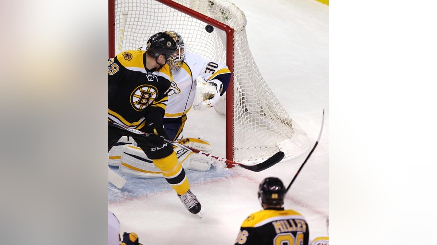 Boston Bruins defenseman Kevan Miller (86) finds the top corner of the net for a goal as Nashville Predators goalie Carter Hutton (30) is shielded by Bruins left wing Matt Beleskey (39) during the first period of an NHL hockey game in Boston, Monday, Dec. 7, 2015. (AP Photo/Charles Krupa)