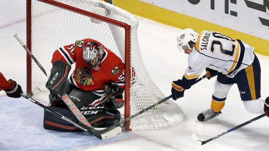 Chicago Blackhawks goalie Corey Crawford, left, makes a save on a shot by Nashville Predators left wing Miikka Salomaki (20) during the first period of an NHL hockey game Tuesday, Dec. 8, 2015, in Chicago. (AP Photo/Charles Rex Arbogast)