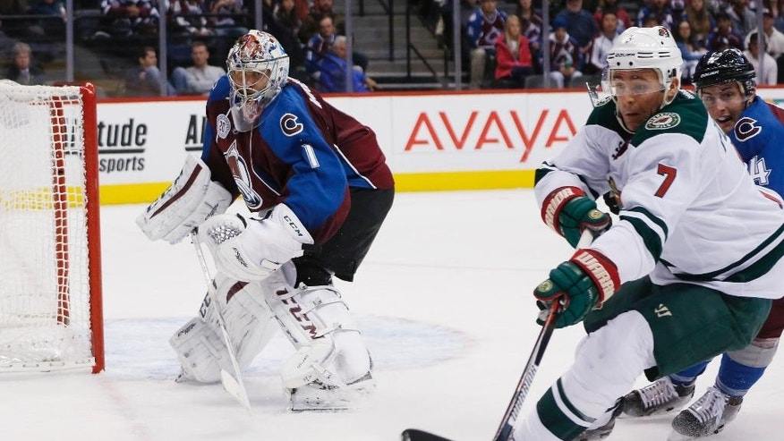Minnesota Wild left wing Chris Porter, front right, reaches for the puck as it is cleared by Colorado Avalanche goalie Semyon Varlamov, left, of Russia, while Avalanche defenseman Tyson Barrie, back right, covers in the second period of an NHL hockey game Monday, Dec. 7, 2015, in Denver. (AP Photo/David Zalubowski)