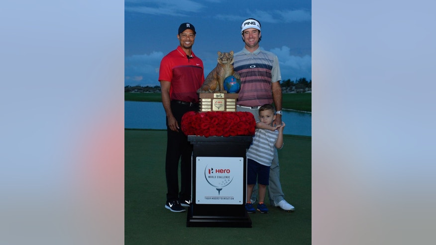 In this photo provided by the Tiger Woods Foundation, tournament host Tiger Woods, left, poses with Bubba Watson and Watson's son, Caleb, after he won the Hero World Challenge in Nassau, Bahamas on Sunday, Dec. 6, 2015. (J.D. Cuban/Tiger Woods Foundation via AP)