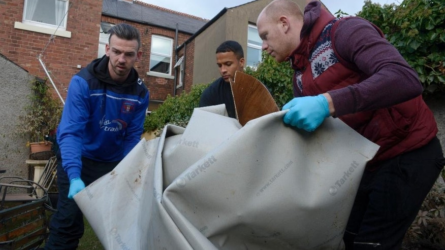 Carlisle United soccer players, left to right,  Michael Raynes, Joe Thompson and Jason Kennedy help to clear items from a flood-damaged home in Carlisle as the club's players offered help to people affected by Storm Desmond, in Carlisle, England, Tuesday Dec. 8, 2015.  Carlisle soccer players pitched in to help with the clear-up after recent stormy weather left many of the country's northern towns and cities severely flooded. (Ben Birchall  / PA via AP) UNITED KINGDOM OUT - NO SALES - NO ARCHIVES