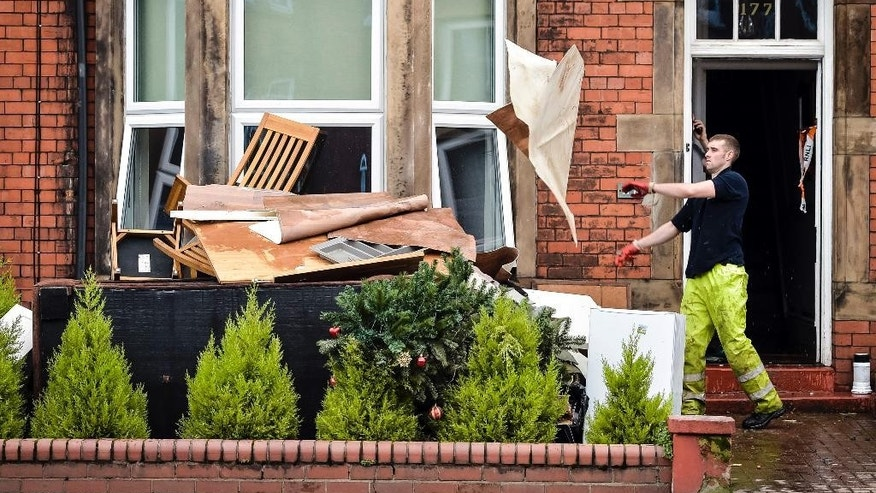 A man throws out furniture, along with a Christmas tree, as the clean-up after the weekend's flood begins in Carlisle northwest England Tuesday Dec. 8, 2015. The northwest England of  was inundated by floods,  after record rainfall led to at least one death and swamped some 3,500 properties over the weekend. (Ben Birchall/PA via AP) UNITED KINGDOM OUT