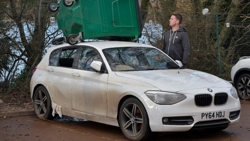 Carlisle United soccer player Dan Hanford surveys flood damage to his car after he left it parked outside the club's ground, in Carlisle, England, Tuesday Dec. 8, 2015. The goalkeeper said the waters carried a large bin and dumped it on the roof of his car.  The army was called in to help, and Carlisle soccer players pitched in to help with the clear-up after stormy weather left many of the country's northern towns and cities severely flooded. (Ben Birchall  / PA via AP) UNITED KINGDOM OUT - NO SALES - NO ARCHIVES