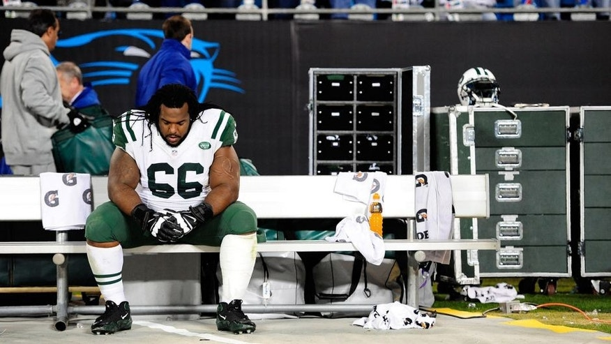 CHARLOTTE, NC - DECEMBER 15: Willie Colon #66 of the New York Jets sits alone on the bench after a loss to the Carolina Panthers at Bank of America Stadium on December 15, 2013 in Charlotte, North Carolina. The Panthers won 30-20. (Photo by Grant Halverson/Getty Images)