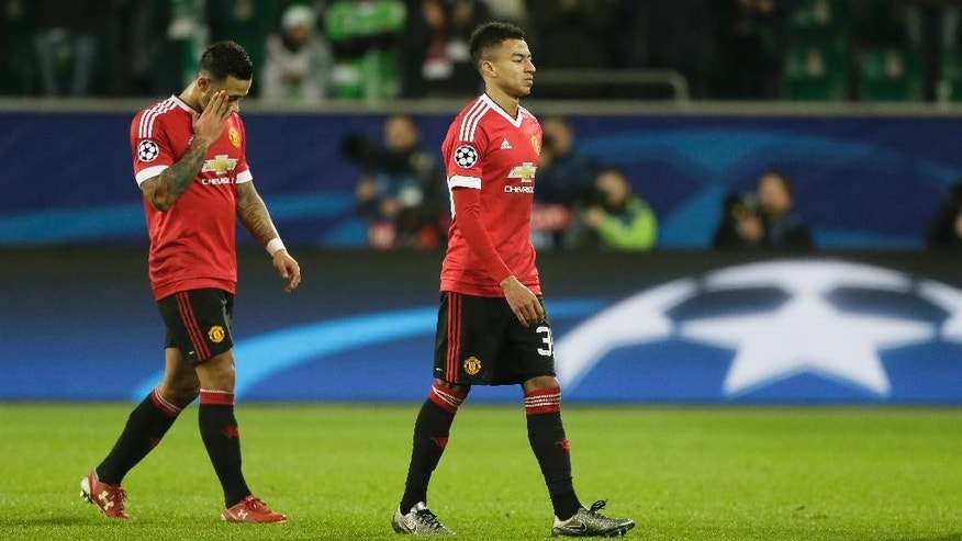 Manchester United's Memphis Depay, left, and Manchester United's Jesse Lingard leave the field after their team lose the Champions League group B soccer match between VfL Wolfsburg and Manchester United in Wolfsburg, Germany, Tuesday, Dec. 8, 2015. (AP Photo/Markus Schreiber)