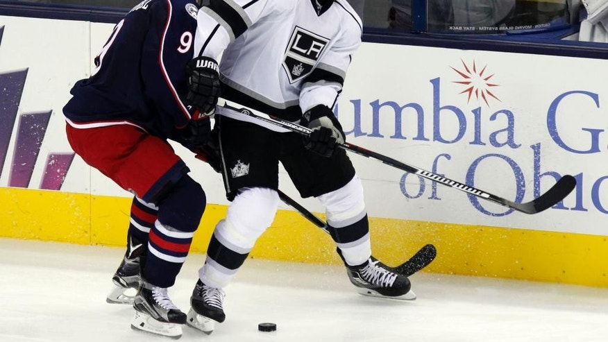 Los Angeles Kings' Christian Ehrhoff, right, works for the puck against Columbus Blue Jackets' Gregory Campbell during the third period of an NHL hockey game in Columbus, Ohio, Tuesday, Dec. 8, 2015. Los Angeles won 3-2 in overtime. (AP Photo/Paul Vernon)