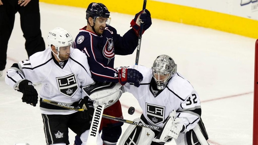 Los Angeles Kings' Alec Martinez (27) and goalie Jonathan Quick (32) work against Columbus Blue Jackets' Nick Foligno (71) during the third period of an NHL hockey game in Columbus, Ohio, Tuesday, Dec. 8, 2015. Los Angeles won 3-2 in overtime. (AP Photo/Paul Vernon)