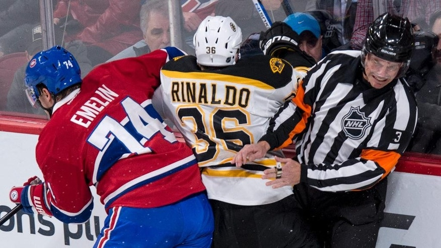 Referee Mike Leggo gets caught along the boards in a check by Montreal Canadiens' Alexei Emelin (74) to Boston Bruins' Zac Rinaldo during first period NHL hockey action, in Montreal, on Wednesday, Dec. 9, 2015. (Paul Chiasson/The Canadian Press via AP)