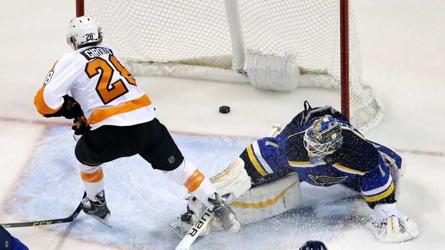 Philadelphia Flyers' Claude Giroux, left, scores past St. Louis Blues goalie Brian Elliott during the second period of an NHL hockey game Thursday, Dec. 10, 2015, in St. Louis. (AP Photo/Jeff Roberson)