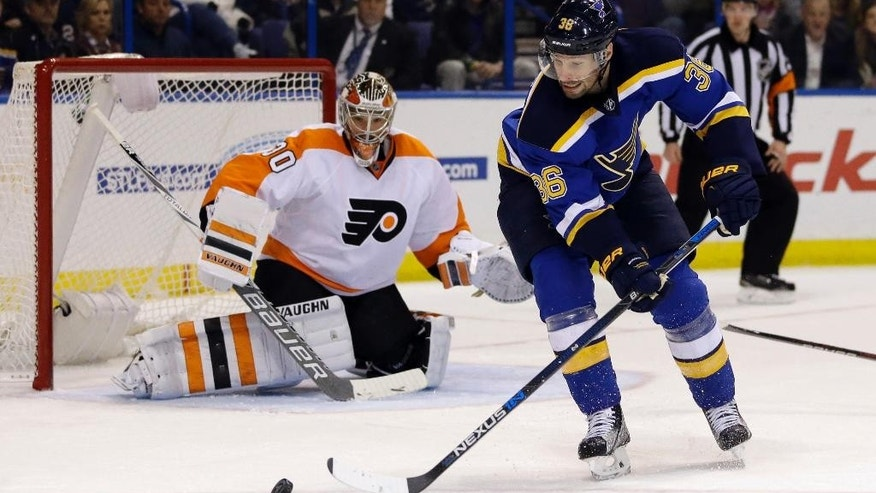 St. Louis Blues' Troy Brouwer, right, reaches for a loose puck as Philadelphia Flyers goalie Michal Neuvirth, of the Czech Republic, defends during the second period of an NHL hockey game Thursday, Dec. 10, 2015, in St. Louis. (AP Photo/Jeff Roberson)