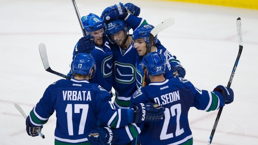Vancouver Canucks' Radim Vrbata, from left, Henrik Sedin, Alexander Edler, Alex Burrows and Daniel Sedin, celebrate Edler's goal against the New York Rangers during the third period of an NHL hockey game in Vancouver, British Columbia, Wednesday, Dec. 9, 2015. (Darryl Dyck/The Canadian Press via AP) MANDATORY CREDIT