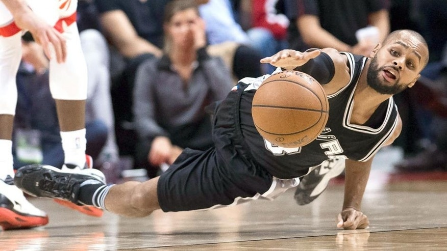 San Antonio Spurs' guard Patty Mills (8) reaches for the ball on the floor during the second half of an NBA basketball game against the Toronto Raptors in Toronto, Wednesday, Dec. 9, 2015. (Nathan Denette/The Canadian Press via AP) MANDATORY CREDIT