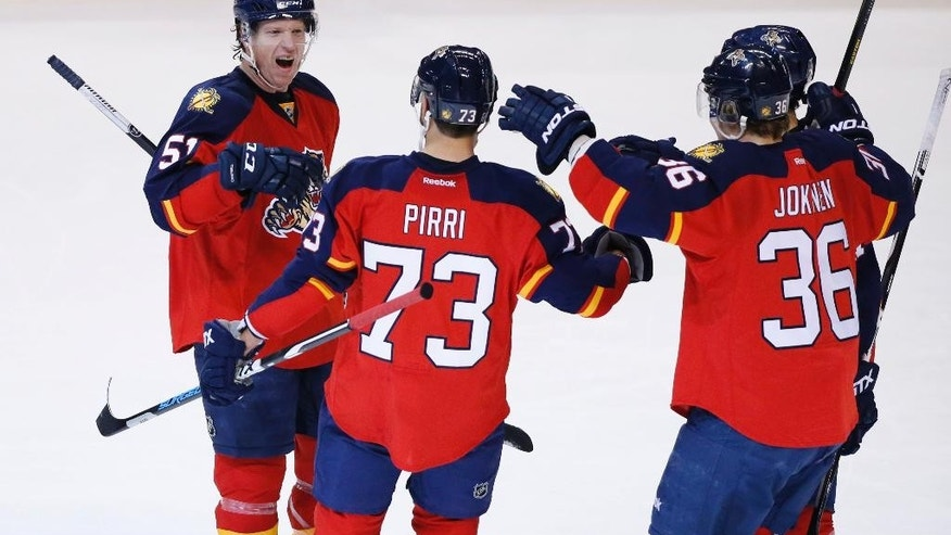 Teammates congratulate Florida Panthers center Brandon Pirri (73) after Pirri scored during the second period of an NHL hockey game against the Washington Capitals, Thursday, Dec. 10, 2015 in Sunrise, Fla. (AP Photo/Wilfredo Lee)