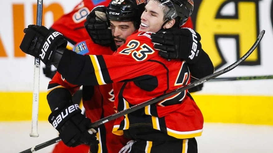 Calgary Flames' Sean Monahan, right, celebrates his goal with teammate Brandon Bollig during second-period NHL hockey game action against the Buffalo Sabres in Calgary, Thursday, Dec. 10, 2015. (Jeff McIntosh/The Canadian Press via AP) MANDATORY CREDIT