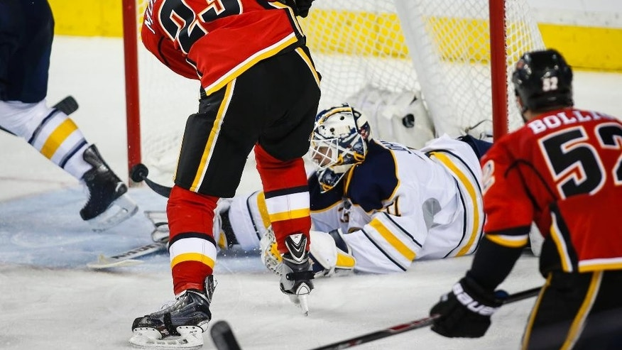 Buffalo Sabres' goalie Chad Johnson, right, lets in a goal from Calgary Flames' Sean Monahan during second-period NHL hockey game action in Calgary, Thursday, Dec. 10, 2015. (Jeff McIntosh/The Canadian Press via AP) MANDATORY CREDIT