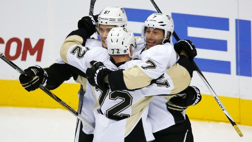 Pittsburgh Penguins center Matt Cullen, right, celebrates scoring a goal with right wing Patric Hornqvist, center, of Sweden, and left wing Sergei Plotnikov, of Russia, against the Colorado Avalanche in the first period of an NHL hockey game, Wednesday, Dec. 9, 2015, in Denver. (AP Photo/David Zalubowski)