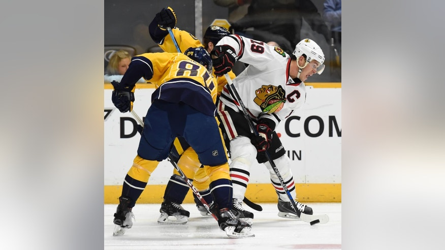 Chicago Blackhawks center Jonathan Toews (19) passes the puck as he is defended by Nashville Predators center Colton Sissons, right, in the first period of an NHL hockey game Thursday, Dec. 10, 2015, in Nashville, Tenn. (AP Photo/Mark Zaleski)