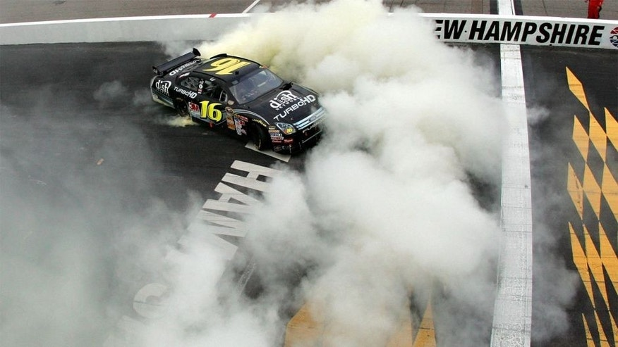 LOUDON, NH - SEPTEMBER 14: Greg Biffle, driver of the #16 Dish Network Turbo HD Ford, does a burnout following his victory in the NASCAR Sprint Cup Series Sylvania 300 at New Hampshire Motor Speedway on September 14, 2008 in Loudon, New Hampshire. (Photo by Chris Trotman/Getty Images for NASCAR)