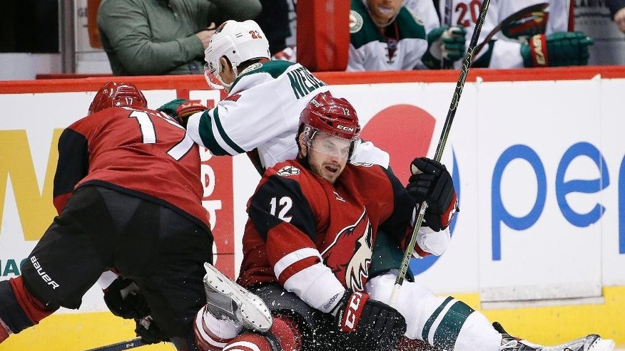 Arizona Coyotes' Brad Richardson (12), Steve Downie (17) and Minnesota Wild's Nino Niederreiter (22), of Switzerland, collide as they all go after the puck during the second period of an NHL hockey game Friday, Dec. 11, 2015 in Glendale, Ariz. (AP Photo/Ross D. Franklin)