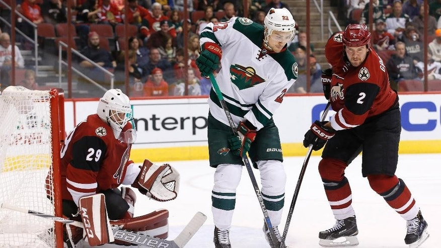 Minnesota Wild's Nino Niederreiter (22), of Switzerland, and Arizona Coyotes' Nicklas Grossmann (2), of Sweden, wait for the puck in front of Coyotes goalie Anders Lindback (29), of Sweden, during the first period of an NHL hockey game Friday, Dec. 11, 2015 in Glendale, Ariz. (AP Photo/Ross D. Franklin)