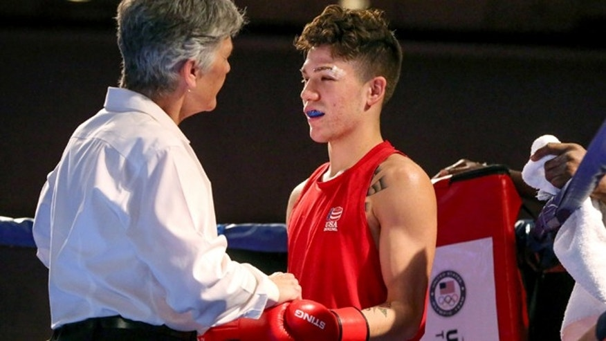 In this photo taken on Wednesday, Dec. 9, 2015, an unidentified boxing referee checks a cut on competitor Nico Hernandez prior to a bout in the U.S. Olympic Boxing Trials in Reno, Nev. Facial cuts have become a problem for many Olympic boxing hopefuls fighting toward the Rio Games, where they wonât wear headgear. Cuts have sidelined several boxers at the normally bloodless U.S. team trials this week, adding fuel to the complaints of athletes and trainers who believe head guards are safer and more practical for Olympic-style competition. (AP Photo/Cathleen Allison)