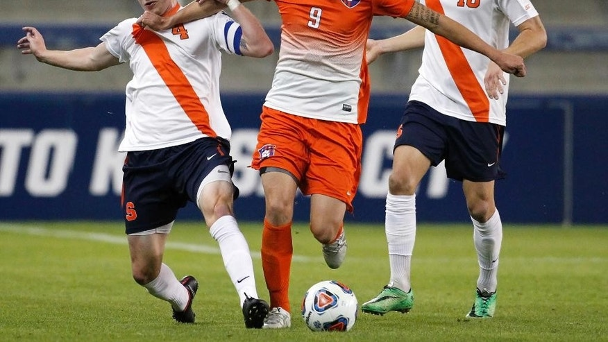 Clemson forward Diego Campos (9) is pressured by Syracuse defender Liam Callahan (4) and midfielder Julian Buescher (10) in the first half of an NCAA College Cup soccer match, Friday, Dec. 11, 2015, in Kansas City, Kan. (AP Photo/Colin E. Braley)