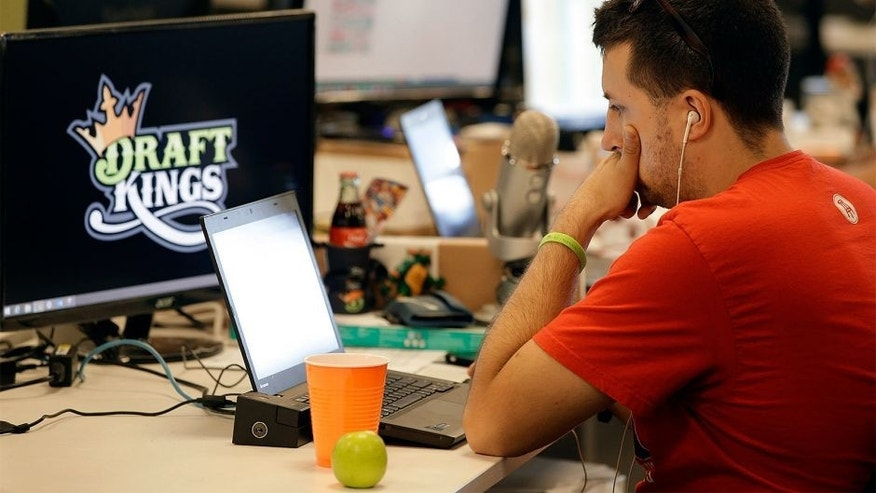 FILE - In this Sept. 9, 2015, file photo, Devlin D'Zmura, a tending news manager at DraftKings, a daily fantasy sports company, works on his laptop at the company's offices in Boston. Nevada has already decided daily fantasy sports are gambling and that people can't put their dollars down on DraftKings and FanDuel until those sites obtain a license in the state. (AP Photo/Stephan Savoia, File)