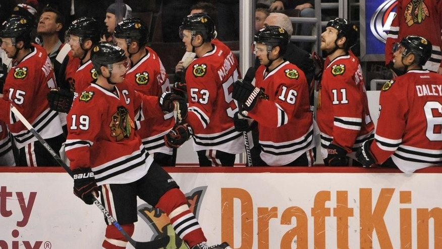 Chicago Blackhawks' Jonathan Toews (19) celebrates with teammates on the bench after scoring a goal during the first period of a hockey game against the Winnipeg Jets, Friday, Dec. 11, 2015, in Chicago. (AP Photo/Paul Beaty)