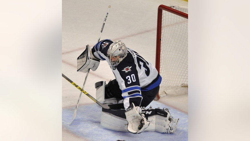 Winnipeg Jets goalie Connor Hellebuyck (30), makes a save during the second period of a hockey game against the Chicago Blackhawks Friday, Dec. 11, 2015, in Chicago. (AP Photo/Paul Beaty)
