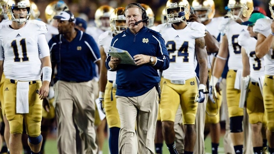 Sep 7, 2013; Ann Arbor, MI, USA; Notre Dame Fighting Irish head coach Brian Kelly (center) leads the team down the field during the timeout between the third and forth quarters against the Michigan Wolverines at Michigan Stadium. Mandatory Credit: Rick Osentoski-USA TODAY Sports